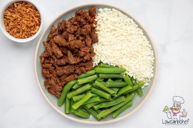 Met dit recept maak je gemakkelijk zelf koolhydraatarme rendang. Dit Indonesische gerecht is lekker om te eten als diner met bloemkoolrijst en sperziebonen. #koolhydraatarm #stoofvlees #avondeten